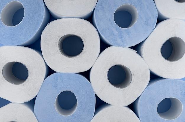 Rolki białego i niebieskiego papieru toaletowego. niedobór papieru toaletowego.