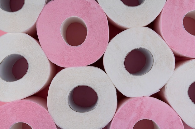 Rolki białego i różowego papieru toaletowego. niedobór papieru toaletowego.