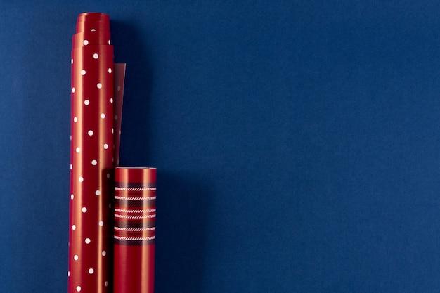 Rolki czerwonego papieru do pakowania na klasycznym niebieskim tle koloru 2020. przygotowania do bożego narodzenia, walentynki 14 lutego. leżał płasko, miejsce, baner.