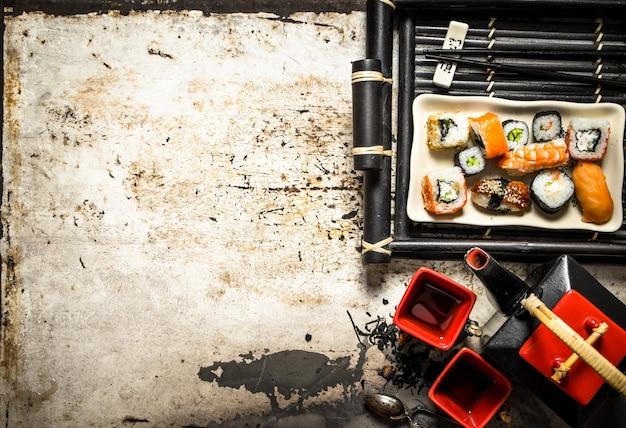 Rolki i sushi na tacy z herbatą ziołową na rustykalnym tle