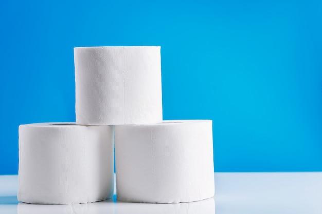 Rolki papieru toaletowego na niebieskim tle. panika zakupów podstawowych towarów. epidemia koronawirusa.
