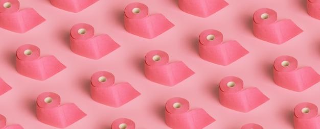 Rolki różowego papieru toaletowego na różowym tle. wzór panoramiczny