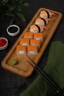 Rolki sushi maki nigiri podawane na jednej na drewnianej desce na ciemnym tle