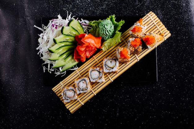 Rolki sushi na macie do sushi z wasabi, imbirem i ogórkiem.