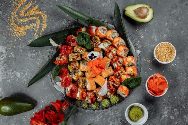 Rolki sushi ustawione na kryształowej tacy. rolls: philadelphia, green dragon, hawaii, red dragon, ebi shake