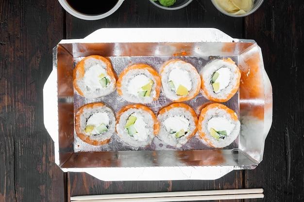 Rolki sushi w zestawie pojemników na wynos, na starym ciemnym tle drewnianego stołu, płaski widok z góry