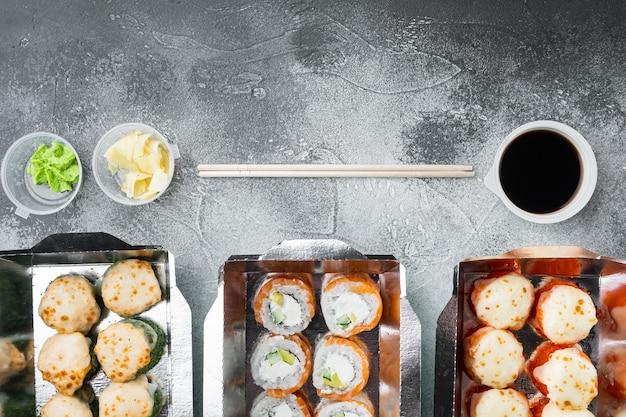 Rolki sushi w zestawie pojemników na wynos, na szarym kamiennym stole, płaski widok z góry