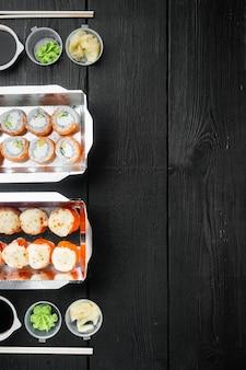 Rolki sushi w zestawie pojemników na wynos, na tle czarnego drewnianego stołu, płaski widok z góry, z copyspace i miejscem na tekst