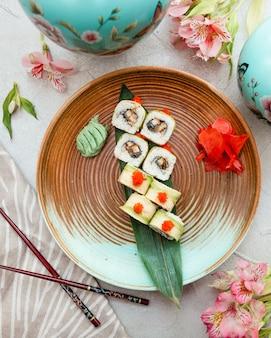 Rolki sushi wewnątrz niebiesko-brązowej płytki.
