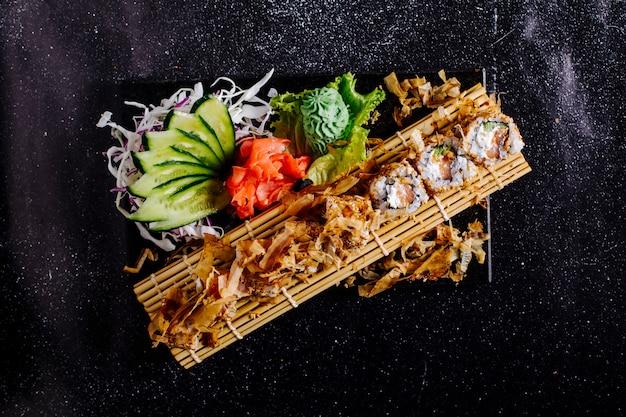 Rolki sushi z frytkami i przystawkami na macie do sushi.