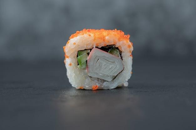 Rolki sushi z łososia samodzielnie na czarnym stole.
