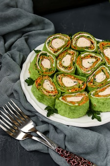 Roll lavash z paluszkami krabowymi w koreańskim stylu na talerzu na ciemnym tle