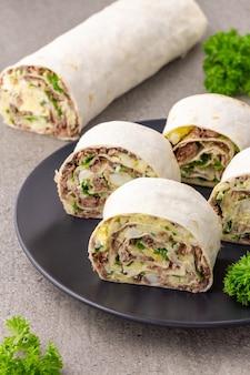 Roll lavash z rybą, serem, jajkiem i pietruszką na szarej powierzchni
