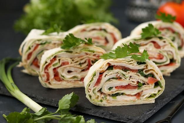 Roll lavash z wędzonym kurczakiem, pomidorami, serem i zielenią znajduje się na ciemnym tle
