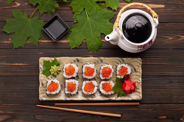 Roll sushi z czerwonym kawiorem na talerzu z wasabi, imbirem, liśćmi klonu i pałeczkami do sushi, na drewnianym tle, widok z góry