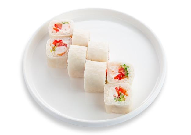 Roll sushi z krewetkami i warzywami. na białym talerzu ceramicznym. białe tło. odosobniony.