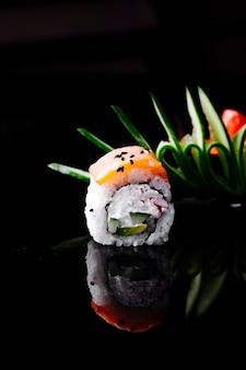 Roll sushi z łososiem i twarogiem w ciemnej przestrzeni.
