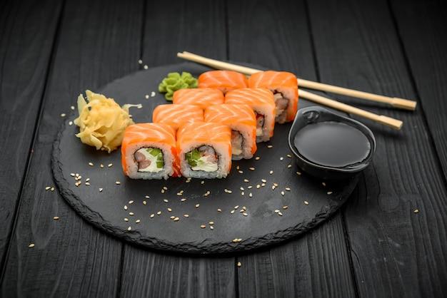 Roll sushi z łososiem, kremowy ser na czarnym tle.