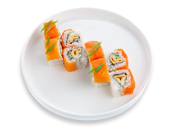 Roll sushi z łososiem, omletem i warzywami. na białym talerzu ceramicznym. białe tło. odosobniony.