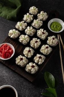 Roll Sushi Z łososiem, Wędzonym Węgorzem, Awokado, Serkiem Na Czarnym Tle Premium Zdjęcia