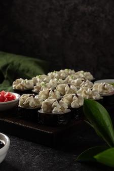 Roll sushi z łososiem, wędzonym węgorzem, awokado, serkiem na czarnym tle