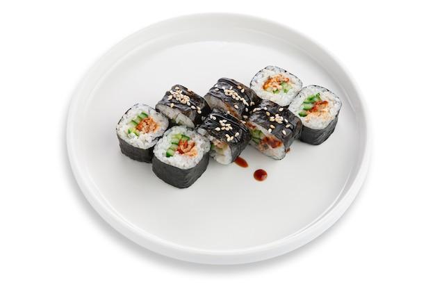 Roll sushi z pieczonym łososiem, ogórkiem i sezamem. wegetariański. na białym talerzu ceramicznym. białe tło. odosobniony.
