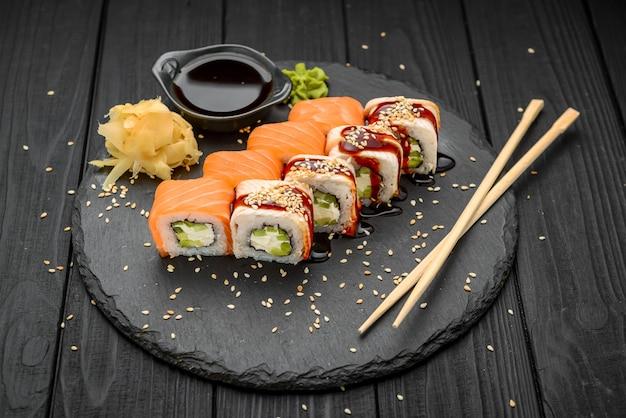 Roll sushi z węgorzem i łososiem na czarno