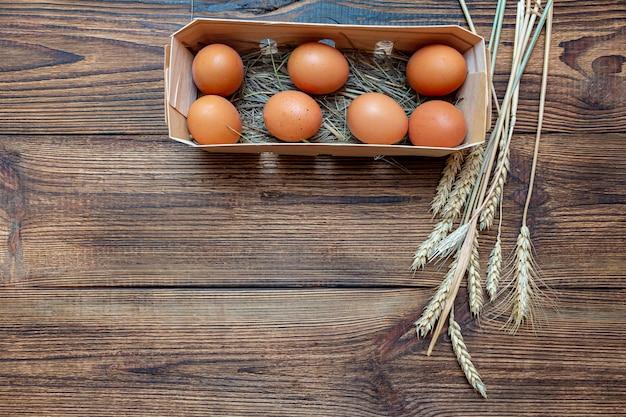 Rolne brązowe jaja ze słomką w drewnianym pudełku brzozy. tło zbliżenie z miejsca na kopię