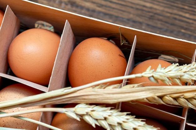 Rolne jaja brązowe ze słomą w pudełku z kory brzozy z bliska