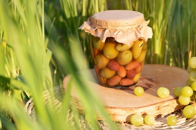 Rolne oliwki w słoju na trawie w słonecznym dniu.