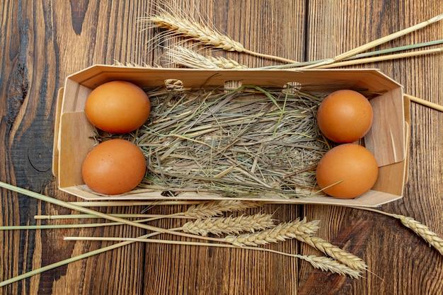 Rolni brown jajka z słomą w brzozy barkentynie boksują zakończenie z kopii przestrzenią