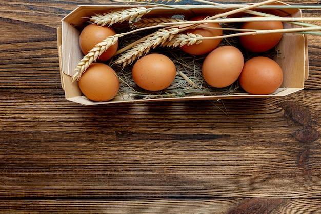 Rolni brown jajka z słomą w brzozy pudełka drewnianym zakończeniu z kopii przestrzenią
