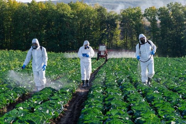 Rolnicy rozpylający pestycydy w masce polowej zbierają trzy chemikalia ochronne