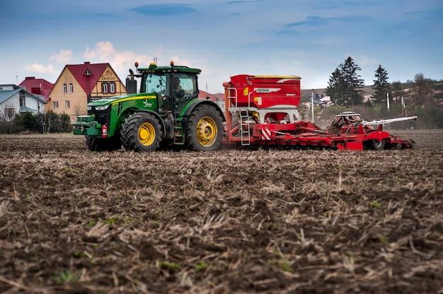 Rolnicy sieją, aplikują nawóz za pomocą ciągnika john deere 8370r z siewnikiem pottinger terrasem c8 na zaoranym polu