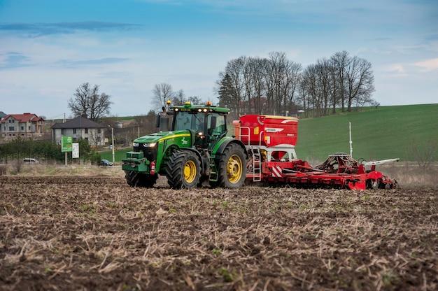 Rolnicy sieją, nawożą za pomocą ciągnika john deere 8370r z siewnikiem pottinger terrasem c8 na zaoranym polu wieczorem