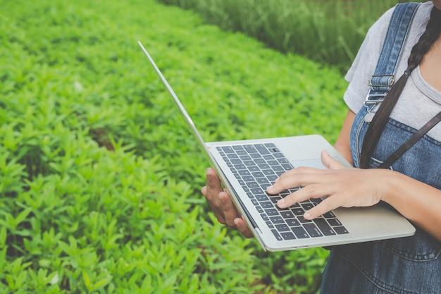 Rolnicza kobieta, która sprawdza rośliny za pomocą tabletek hodowlanych - nowoczesna koncepcja