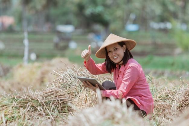 Rolniczki noszą kapelusz z kciukami do góry podczas kucania z tabletem na polach ryżowych