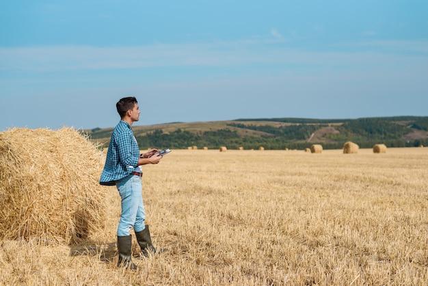 Rolnik agronom w dżinsach, koszula z tabletem jest w polu ze stosem, z tabletem patrząc w dal.