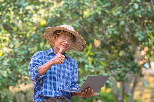 Rolnik azji z koncepcja smartphone i laptop, biznes i technologia