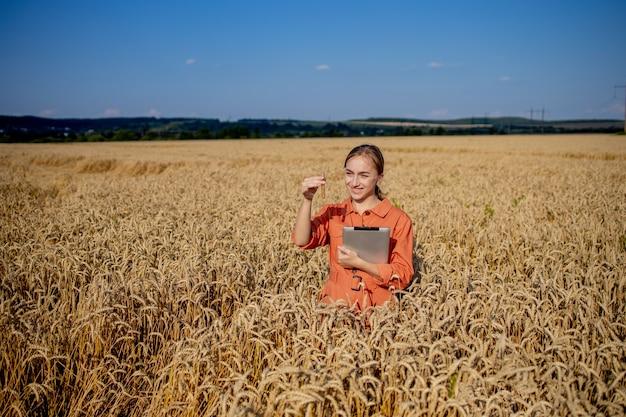 Rolnik badający roślinę w polu pszenicy. w dłoni trzyma szklaną probówkę zawierającą badaną substancję