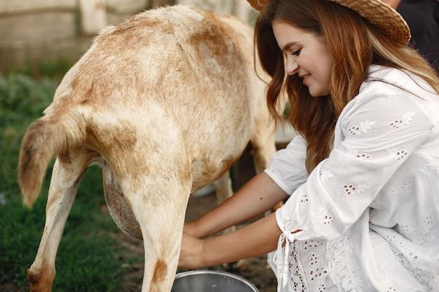 Rolnik dziewczyna z białą kozą. kobieta i mała kózka zielona trawa. gospodarstwo ekologiczne. koncepcja gospodarstwa i rolnictwa. zwierzęta wiejskie. dziewczyna molkuje kozę.