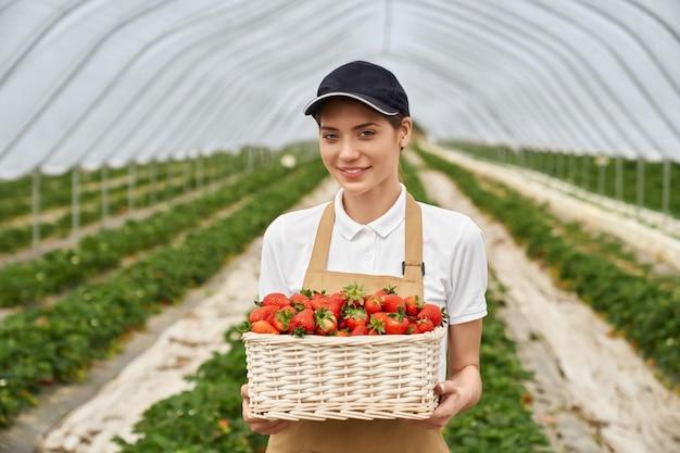 Rolnik kobieta trzyma wiklinowy kosz z pysznymi truskawkami