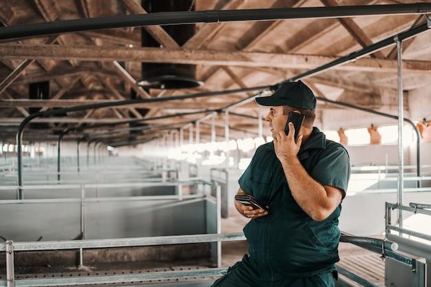 Rolnik korzystający ze smartfona i dzwoniąc do dystrybutora zwierząt