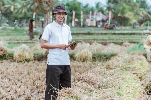 Rolnik, który jest właścicielem pola ryżowego, uśmiecha się, stojąc trzymając podkładkę na polu ryżowym