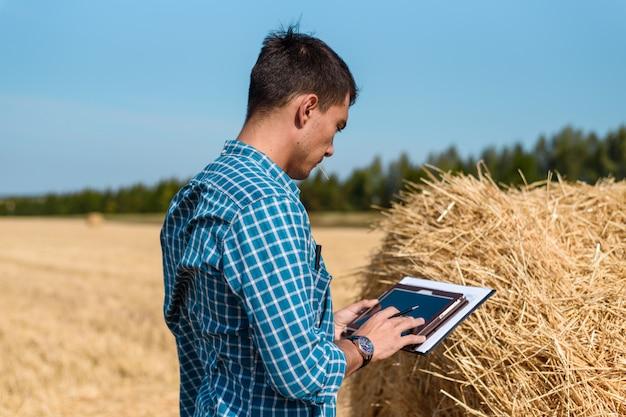 Rolnik-mężczyzna używa tabletu na polu obok stogu siana