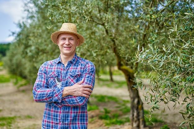 Rolnik mężczyzna w słomkowym kapeluszu na plantacji oliwek.