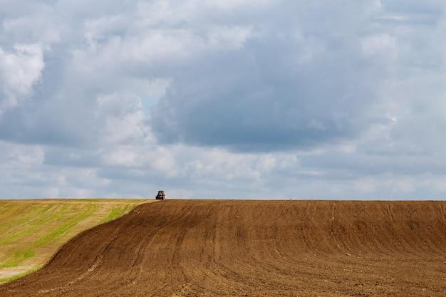 Rolnik na ciągniku orze ziemię przed siewem kultywatorem przedsiewnym