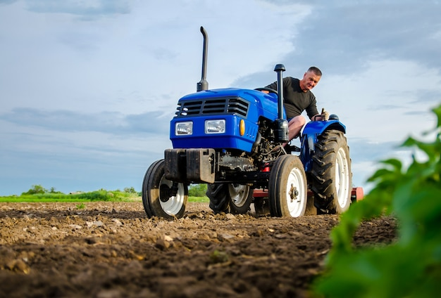 Rolnik na ciągniku pracuje w polu frezowanie gleby kruszenie i spulchnianie gruntu