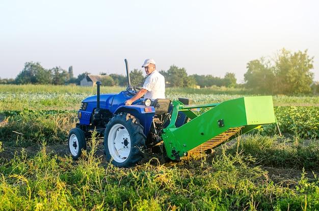 Rolnik na traktorze z agregatem sprzętu do wykopywania ziemniaków