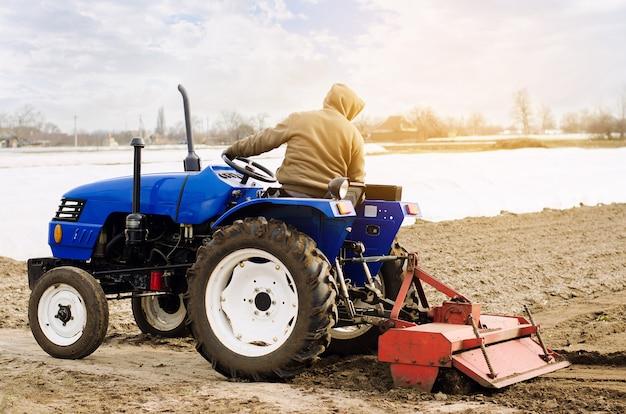 Rolnik na traktorze z frezarką rozluźnia mielonki i miesza glebę. spulchniając powierzchnię